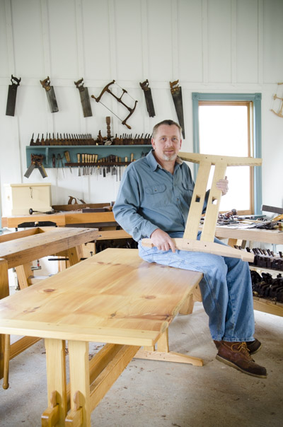 Will Myers sitting on the finished trestle table holding a trestle table leg next to woodworking workbenches in Joshua Farnsworth's woodworking workshop