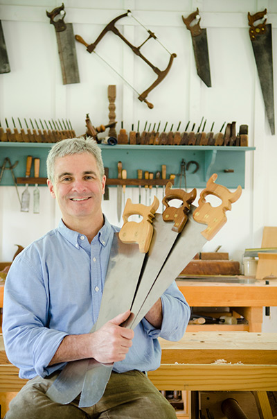 Woodworker Tom Calisto holding three hand saws in a woodworking workshop