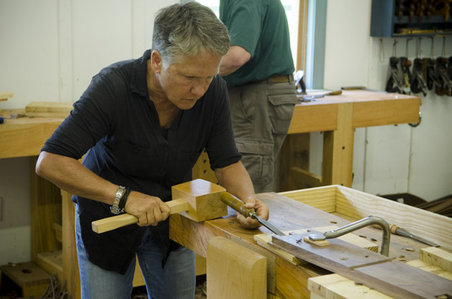 An older female student using a joiner's mallet to hit a chisel while making dovetails