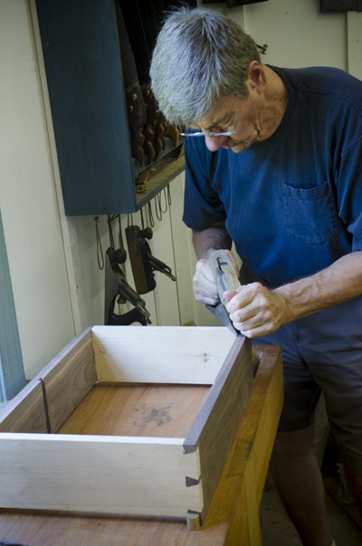 An older male student handplaning a walnut cupboard case with hand planes in the background