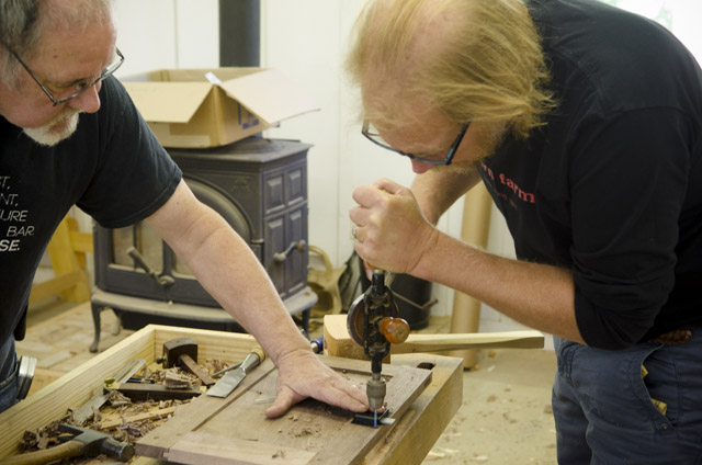 David Ray Pine teaching a student how to drill a door lock in a woodworking school