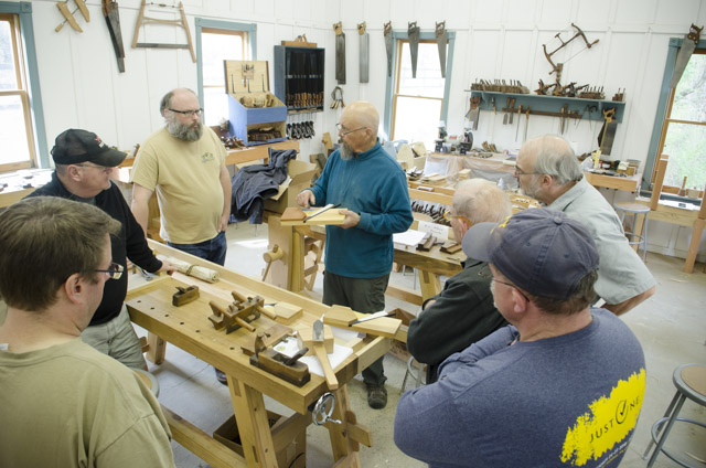 Restoring Wooden Hand plane class with students surrounding Bill Anderson to look at handplane resoration