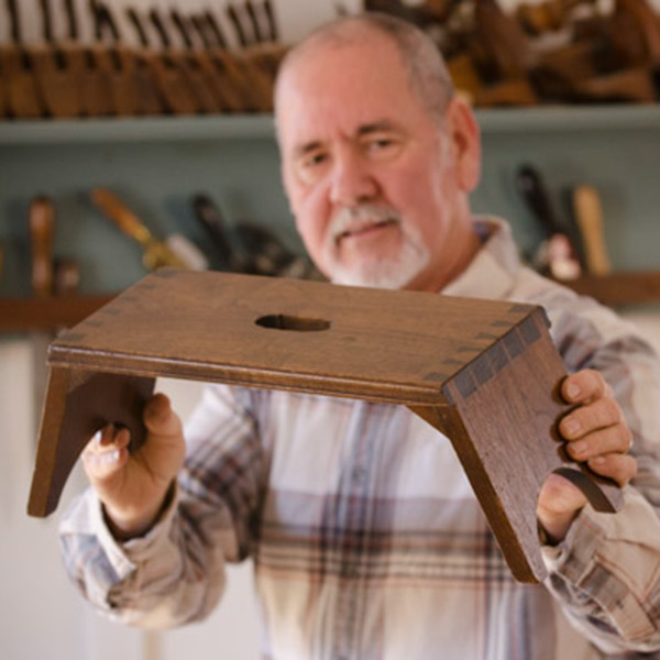 David Ray Pine looking at a dovetailed Moravian footstool in a woodworking school