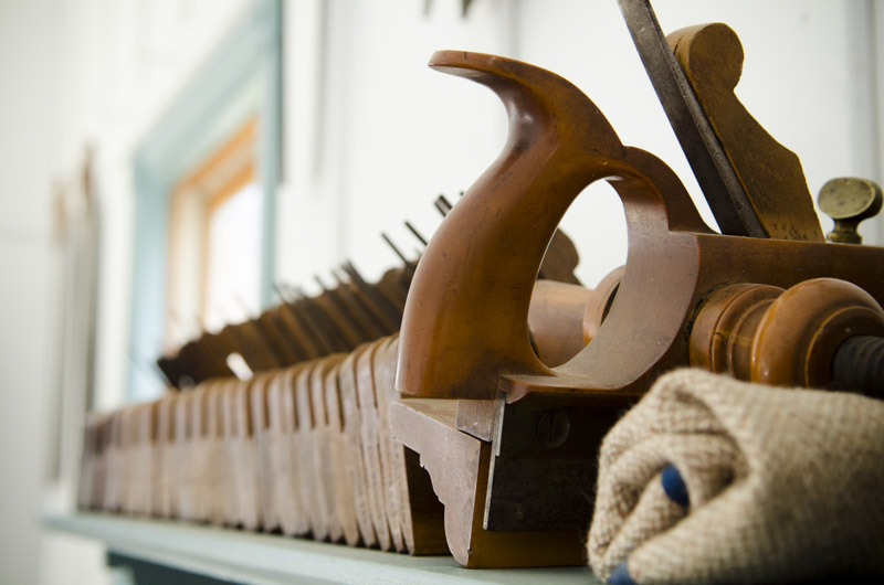 Antique hand planes and plow plane and moulding planes lined up on a blue hand tool shelf in Joshua Farnsworth's Wood And Shop Traditional Woodworking School