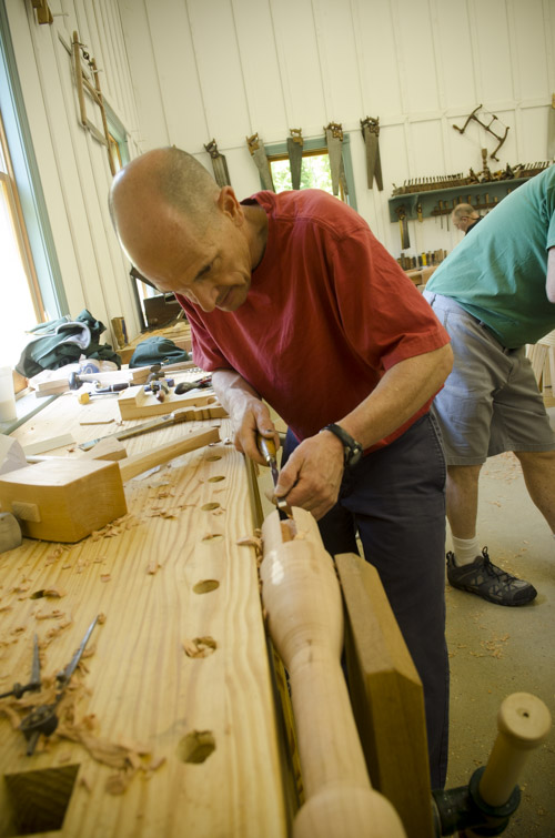a male woodworking student using a chisel to cut a sliding dovetail joint on a table spindle at his workbench at Joshua Farnsworth's Wood And Shop Traditional Woodworking School