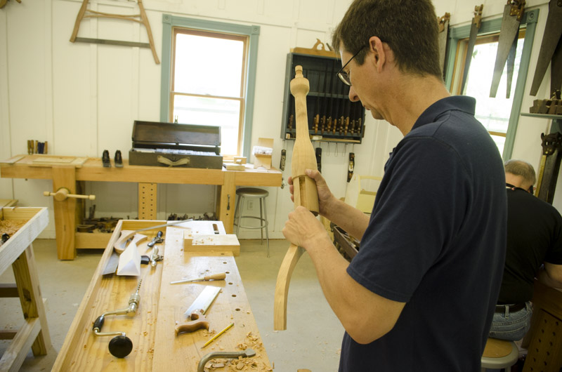 a male woodworking student fitting his sliding dovetail table legs to the spindle at his workbench at Joshua Farnsworth's Wood And Shop Traditional Woodworking School