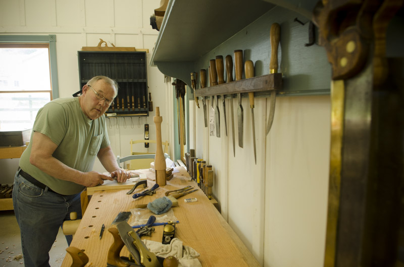 a woodworking student using a chisel at his Roubo workbench at Joshua Farnsworth's Wood And Shop Woodworking School