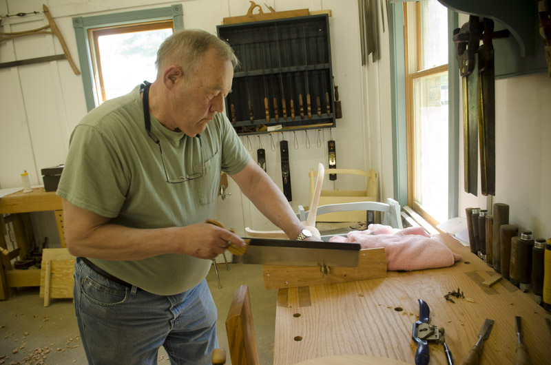 a woodworking student using a dovetail saw at his roubo workbench at Joshua Farnsworth's Wood And Shop Woodworking School