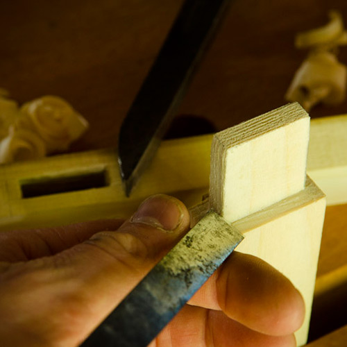 Joshua Farnsworth holding a wood chisel cutting a mortise and tenon joint