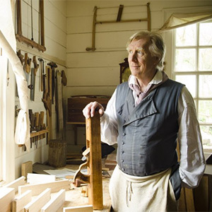 Kaare Loftheim standing with a hand planer next to a wooworking workbench at the Anthony Hay Cabinetmakers Shop at Colonial Williamsburg