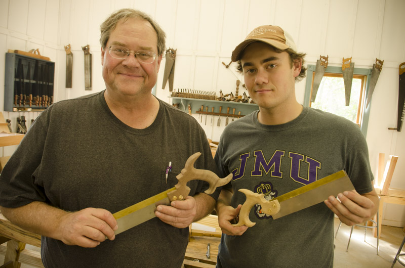 A father and son displaying the dovetail saws they just made at Joshua Farnsworth's Wood And Shop Traditional Woodworking School