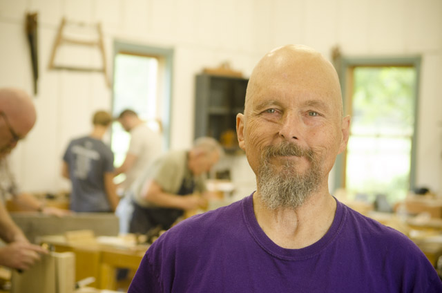 Bill Anderson woodworker at the Wood and Shop Traditional Woodworking School with students in the background