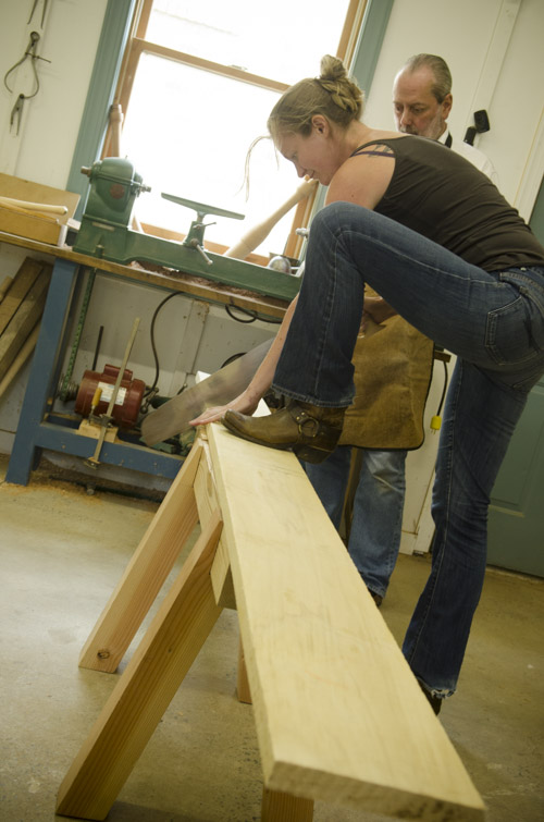 female woodworking student using a crosscut hand saw to cut a poplar boards on saw horses at Joshua Farnsworth's Wood And Shop Woodworking School