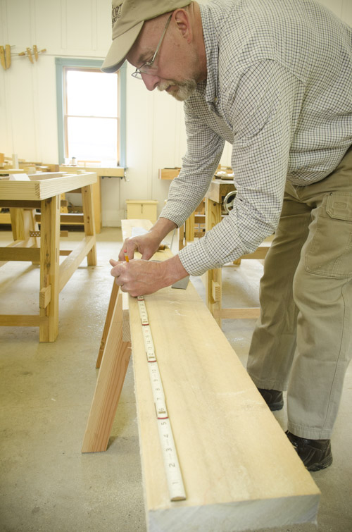 older gentleman woodworking student measuring a piece of poplar lumber with a zig zag rule on sawhorses at Joshua Farnsworth's Wood And Shop Woodworking School