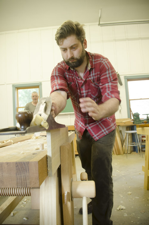 male woodworking student using a stanley bailey No. 7 jointer plane to square a poplar board on a woodworking workbench at Joshua Farnsworth's Wood And Shop Woodworking School