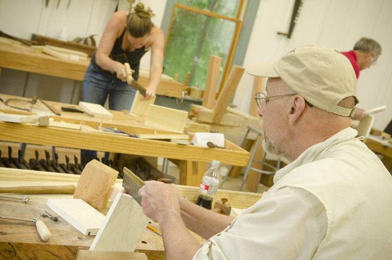 older gentleman woodworking student cutting dovetails with a dovetail saw on a woodworking workbench at Joshua Farnsworth's Wood And Shop Woodworking School