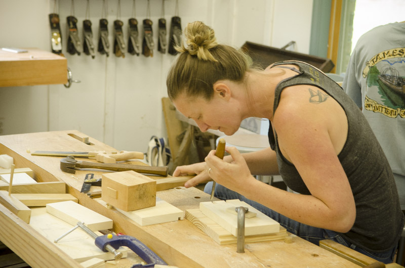 female woodworking student cutting dovetails with joiner's mallet and chisel on a woodworking workbench at Joshua Farnsworth's Wood And Shop Woodworking School