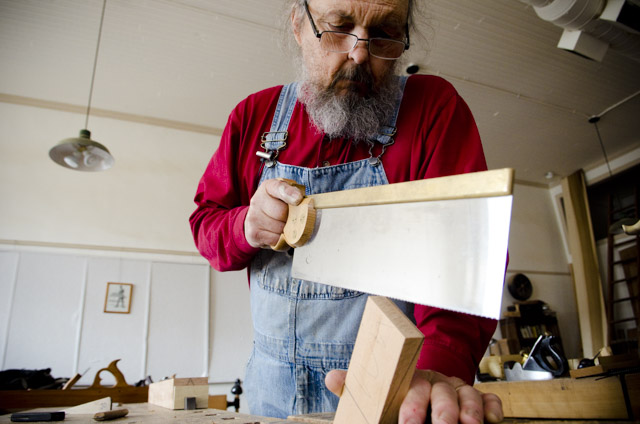 Bill Anderson using a tenon saw while making a wooden bench plane at Roy Underhill's Woodwright's School