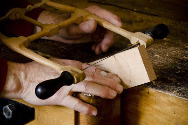 Bill Anderson using a small bow saw to cut out a handplane wedge while making a wooden bench plane