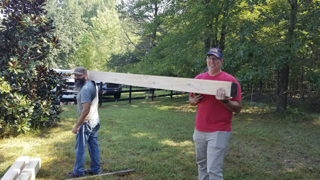 Woodworking Students carrying a heavy beam at a timber framing or timber frame class at the wood and shop traditional woodworking school