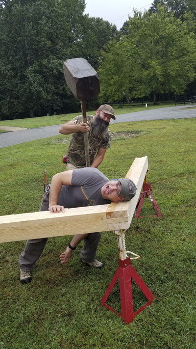 Funny photo of Ervin Ellis pretending to smash the head of a Woodworking Students at a timber framing or timber frame class at the wood and shop traditional woodworking school