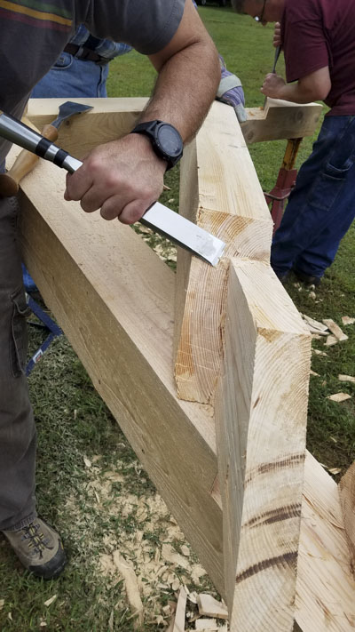 Woodworking Students using a timber frame slick to cut a tenon at a timber framing or timber frame class at the wood and shop traditional woodworking school