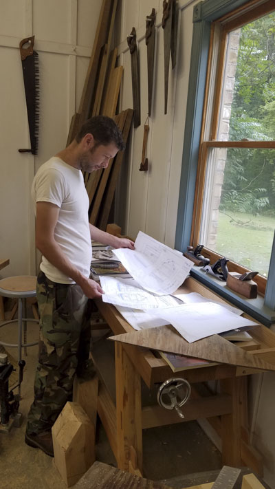 Willie Ellis looking over plans at a timber framing or timber frame class at the wood and shop traditional woodworking school