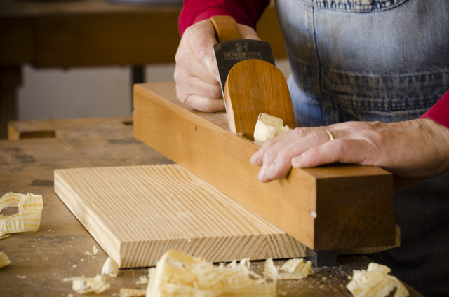 Bill Anderson using a jointer bench plane to flatten a pine panel on a woodworking workbench at Roy Underhill's woodwright's school