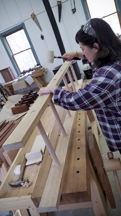 Lady using a rubber mallet to assemble an oak ladder in a ladder making class