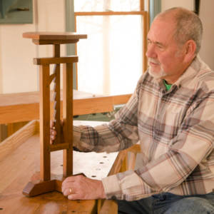 David Ray Pine looking at a ratcheting candle stand table in a woodworking school